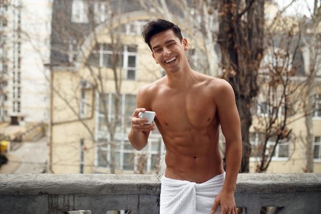 Homme sexy souriant dans une serviette de salle de bain sur le balcon avoir un café breack
