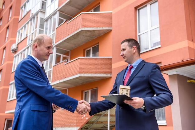 Homme signant un contrat d'achat d'appartement en face d'un nouveau bâtiment