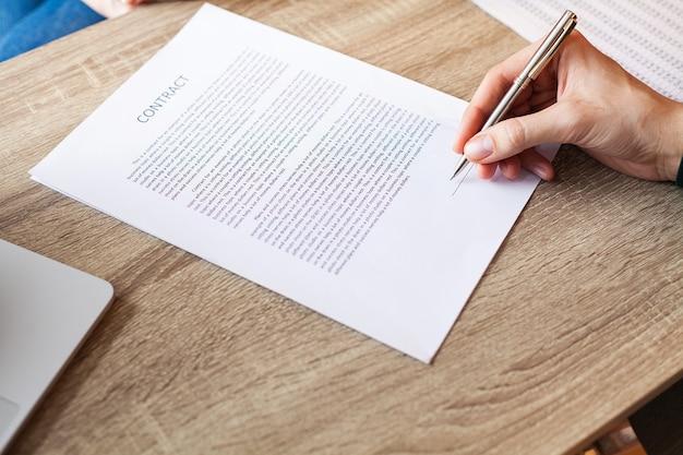 L'homme signe un contrat à un bureau dans un bureau d'entreprise.