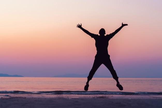 Homme silhouette lever les mains et sauter au concept de liberté du ciel avec ciel coucher de soleil et saison de plage d'été.