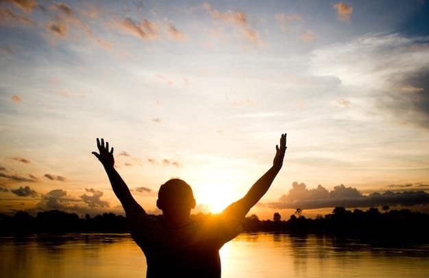 Homme de silhouettes priant la main sur le fond de coucher de soleil magnifique.