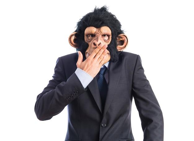 Un homme singe couvrant sa bouche