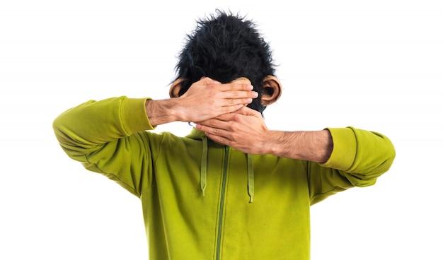 Homme singe couvrant son visage