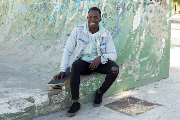 Homme avec skateboard en milieu urbain