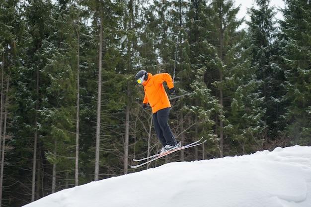 Homme de skieur volant au saut de la pente des montagnes