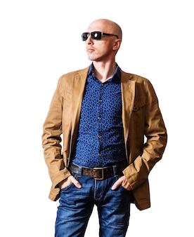 Homme skinhead en lunettes de soleil, veste jaune et jean bleu posant avec ses mains dans ses poches