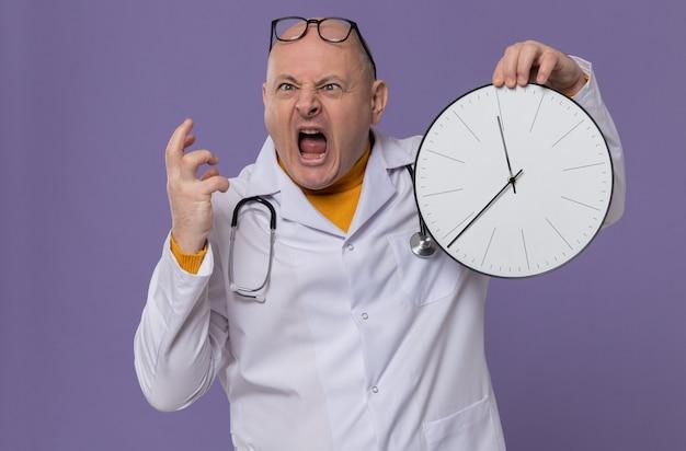Homme slave adulte agacé avec des lunettes optiques en uniforme de médecin avec stéthoscope tenant une horloge et criant sur quelqu'un qui regarde de côté