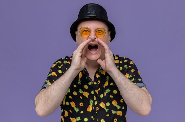 Homme slave adulte anxieux avec chapeau haut de forme noir portant des lunettes de soleil en gardant les mains près de sa bouche et