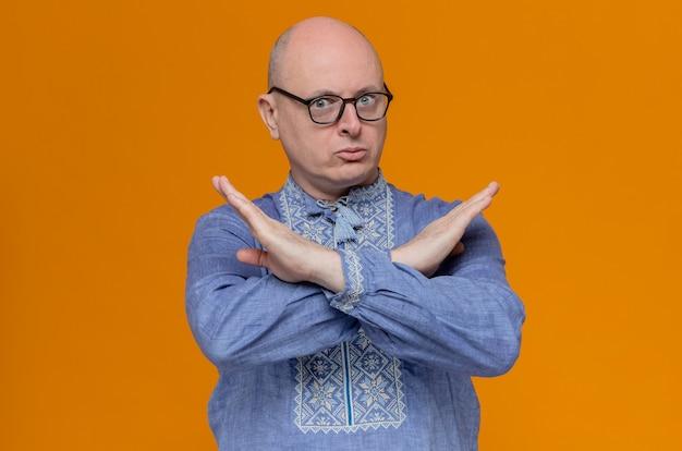 Homme slave adulte anxieux en chemise bleue et avec des lunettes optiques croisant les mains ne faisant aucun signe