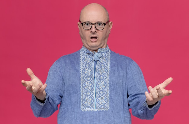 Homme slave adulte choqué en chemise bleue portant des lunettes optiques gardant les mains ouvertes et