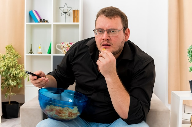 Homme slave adulte choqué dans des lunettes optiques est assis sur un fauteuil tenant la télécommande du téléviseur et un bol de chips sur les jambes à l'intérieur du salon