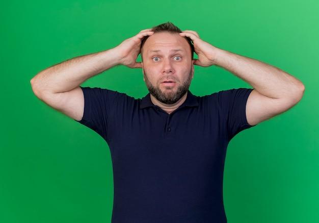 Homme slave adulte choqué à la recherche de mettre les mains sur la tête isolé sur mur vert