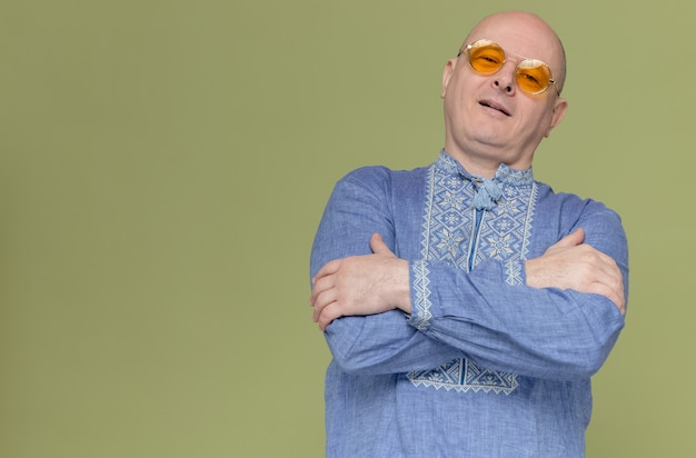 Homme slave adulte confiant en chemise bleue portant des lunettes de soleil debout avec les bras croisés