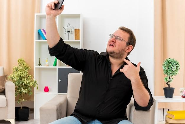 Homme slave adulte confiant dans des lunettes optiques est assis sur un fauteuil en se pointant sur lui-même et en regardant le téléphone en prenant selfie à l'intérieur de la salle de séjour