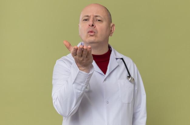 Homme slave adulte confiant en uniforme de médecin avec stéthoscope envoyant un baiser avec sa main