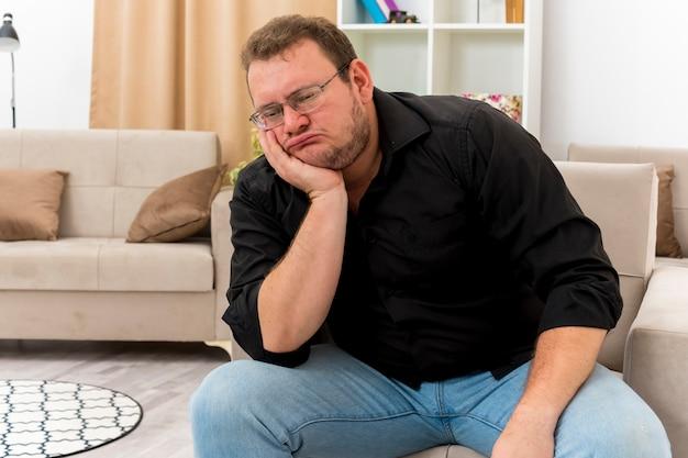 Homme slave adulte déçu dans des lunettes optiques est assis sur un fauteuil tenant le menton et regardant vers le bas à l'intérieur de la salle de séjour