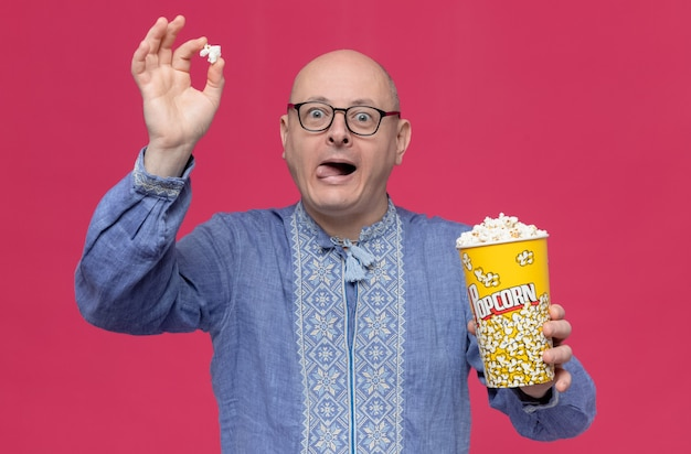 Homme slave adulte excité en chemise bleue portant des lunettes optiques tenant un seau à pop-corn