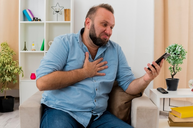 Homme slave adulte excité est assis sur un fauteuil mettant la main sur la poitrine en regardant le téléphone à l'intérieur du salon