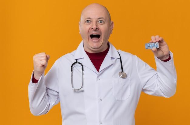 Homme slave adulte excité en uniforme de médecin avec stéthoscope tenant un blister de médicaments et gardant le poing