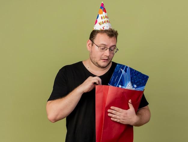 Un homme slave adulte impressionné dans des lunettes optiques portant une casquette d'anniversaire tient et regarde une boîte-cadeau dans un sac à provisions en papier