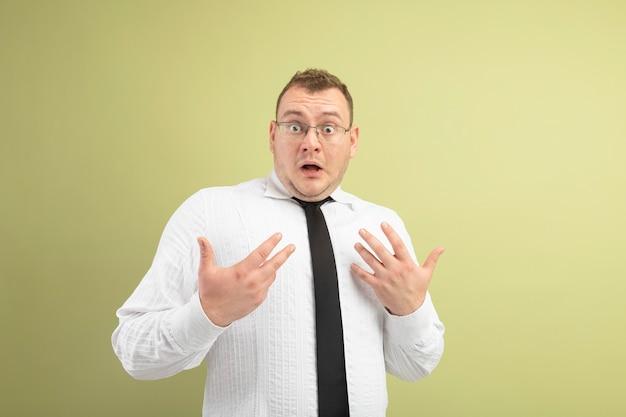 Homme slave adulte impressionné portant des lunettes et une cravate regardant la caméra en se pointant vers lui-même avec les mains isolées sur fond vert olive avec copie espace