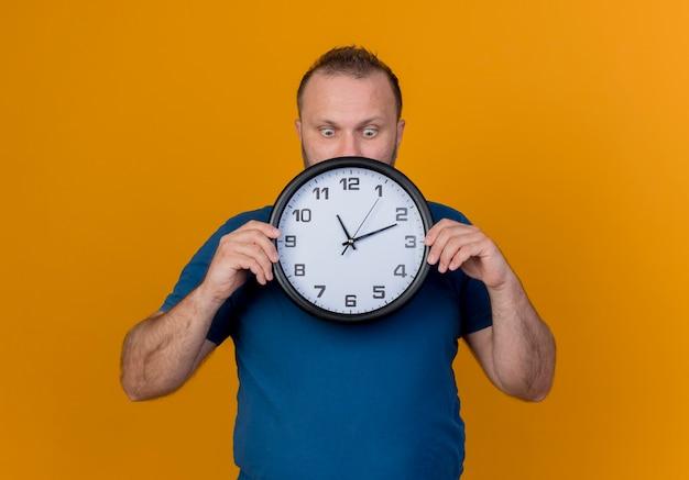 Homme slave adulte impressionné tenant et regardant l'horloge