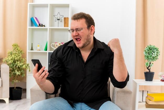 Homme slave adulte joyeux dans des lunettes optiques est assis sur un fauteuil à la recherche de téléphone et de garder le poing à l'intérieur de la salle de séjour conçue
