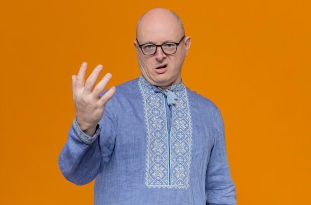 Homme slave adulte mécontent en chemise bleue et avec des lunettes en gardant la main ouverte et à la recherche