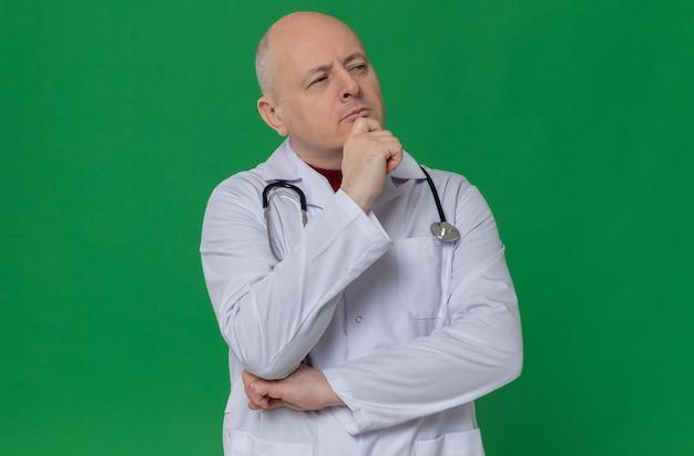 Homme slave adulte réfléchi en uniforme de médecin avec stéthoscope mettant la main sur son menton et regardant de côté