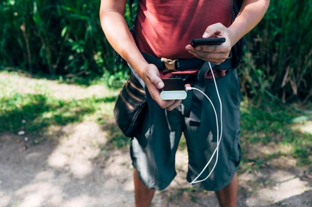 Homme avec smartphone et batterie auxiliaire dans la jungle