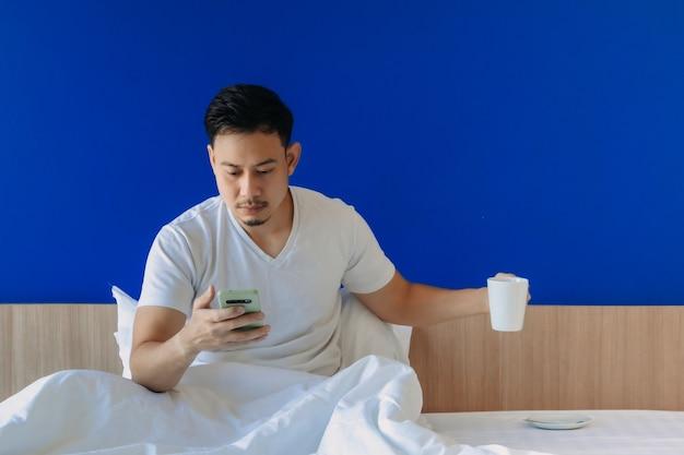 Homme avec smartphone et café sur le lit sur fond d'espace de copie bleu