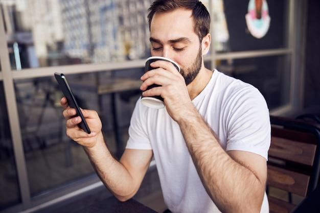 Homme avec smartphone et café