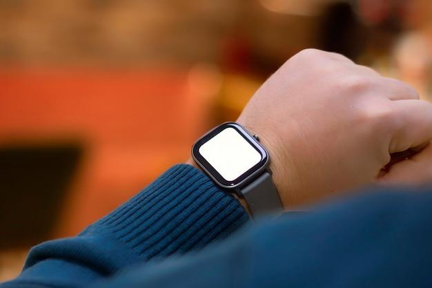 Un homme avec une smartwatch et une maquette d'écran blanc sur sa main. un homme utilise un tracker de fitness sur le fond d'un centre commercial.