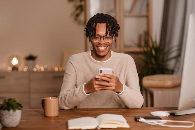 Homme smiley à l'aide de son smartphone à la maison