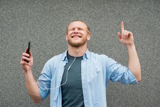 Homme smiley écoutant de la musique sur des écouteurs