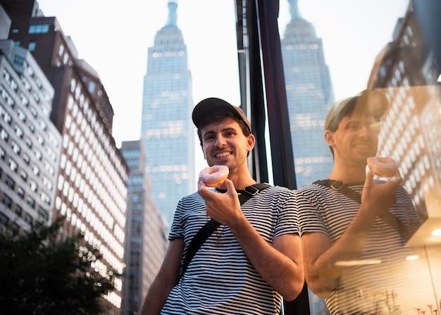 Homme smiley faible angle avec beignet