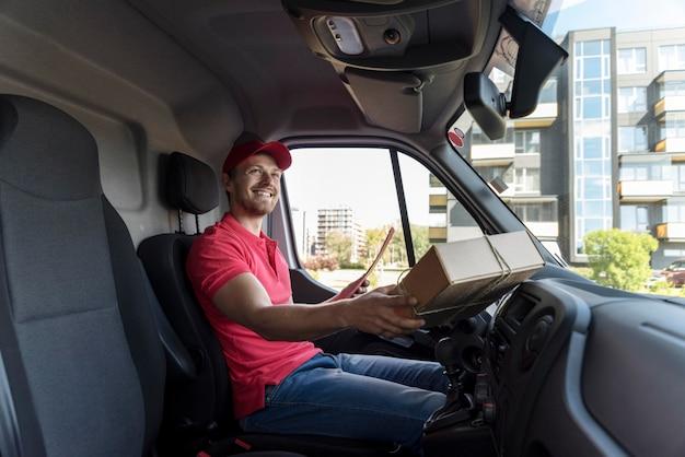 Homme smiley avec paquet en voiture