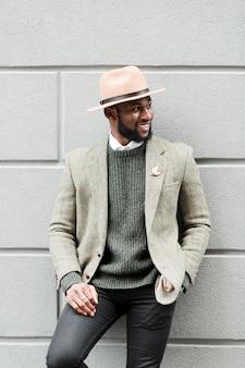 Homme smiley posant sur un mur gris