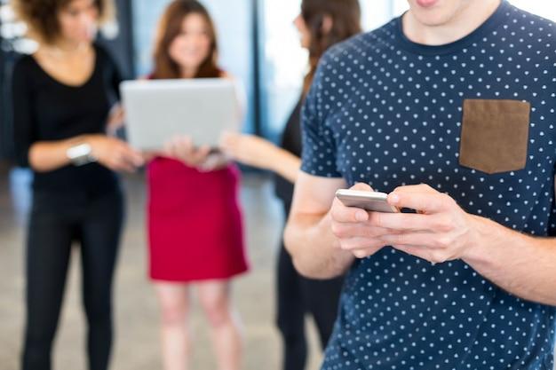Homme sms sur smartphone tandis que ses collègues se tenant derrière elle au bureau