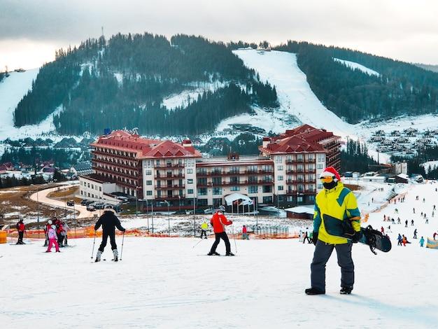 Homme avec snowboard en chapeau de noël rouge en montant par la station de ski des montagnes d'hiver de la colline enneigée