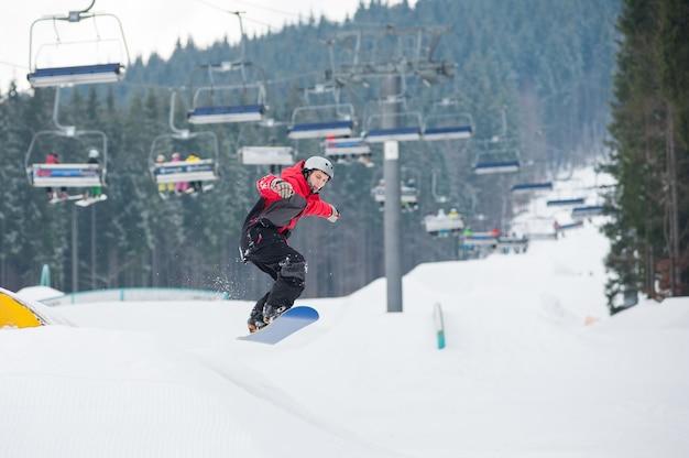 Homme sur le snowboard sautant par-dessus la pente en jour d'hiver