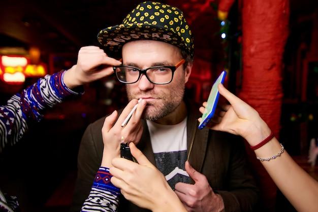 Homme avec des soies dans un bonnet jaune près duquel les mains des femmes tiennent une cigarette, un briquet et un téléphone