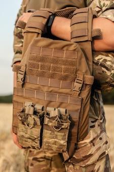 Homme soldat debout contre un champ. soldat en tenue militaire avec gilet pare-balles. photo d'un soldat en tenue militaire tenant un pistolet et un gilet pare-balles sur fond orange du désert.