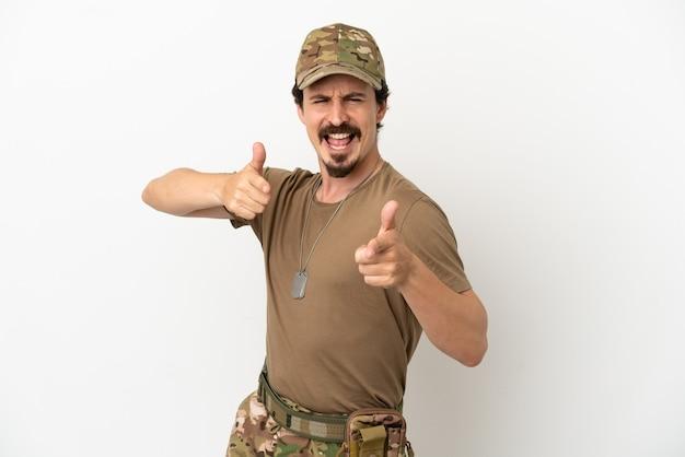 Homme soldat isolé sur fond blanc pointant vers l'avant et souriant