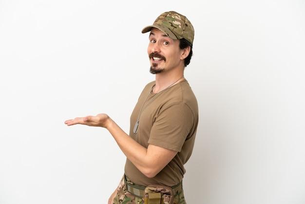Homme soldat isolé sur fond blanc présentant une idée tout en souriant vers
