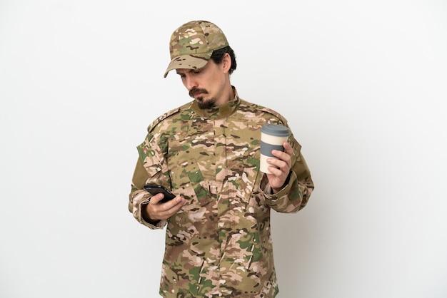 Homme soldat isolé sur fond blanc tenant un café à emporter et un mobile