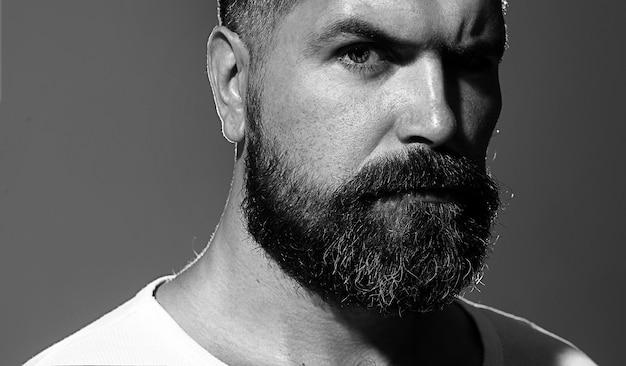 Homme solide avec barbe et moustache. closeup portrait d'homme barbu athlétique. bel homme barbu élégant. homme sexy, macho, longue barbe. hipster barbu caucasien attrayant. noir et blanc.