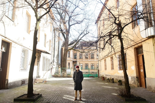 Homme solitaire en manteau gris se tient sur la cour arrière dans une journée ensoleillée