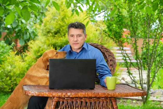 Homme avec son chien boit du café et travaille avec un ordinateur portable dans le jardin