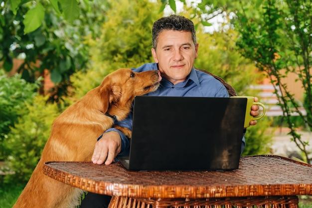 Homme avec son chien buvant du café analysant des informations web et lisant des nouvelles